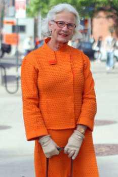 Пожилая женщина в оранжевом костюме